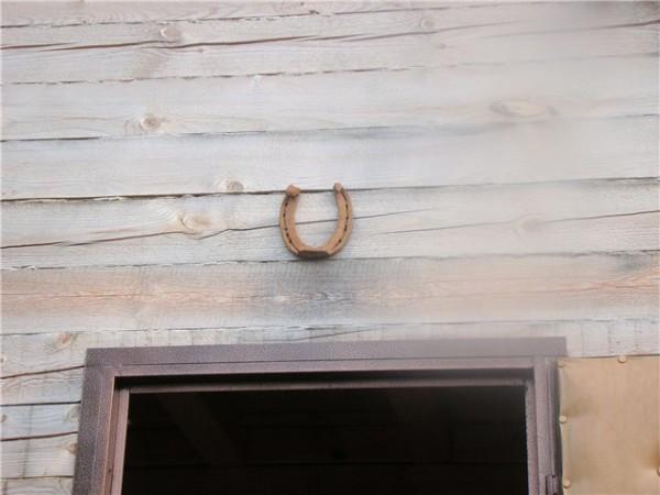 Подкова над дверью в деревянном доме